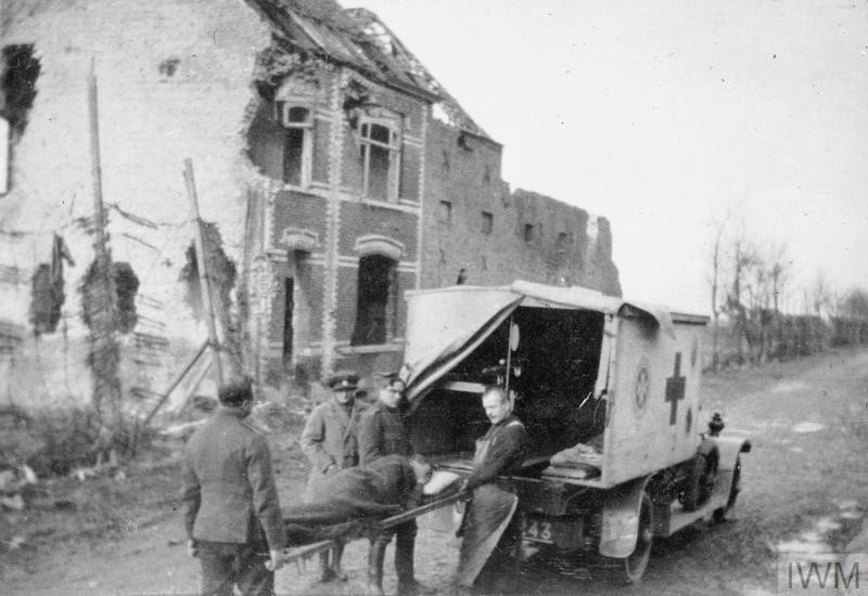 Mairi Chisholm with Belgian orderlies, loading a wounded soldier into the Wolseley Red Cross van in Pervyse, 1917;  © IWM (Q 105943)
