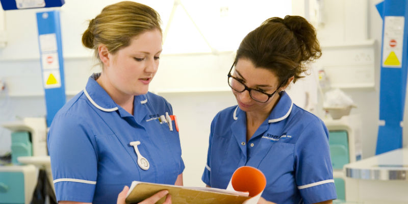 Two nurses on an acute ward looking at patient notes
