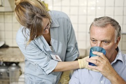 Nursing staff member helping patient to drink a glass of water