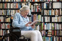 Woman in wheelchair reading a book
