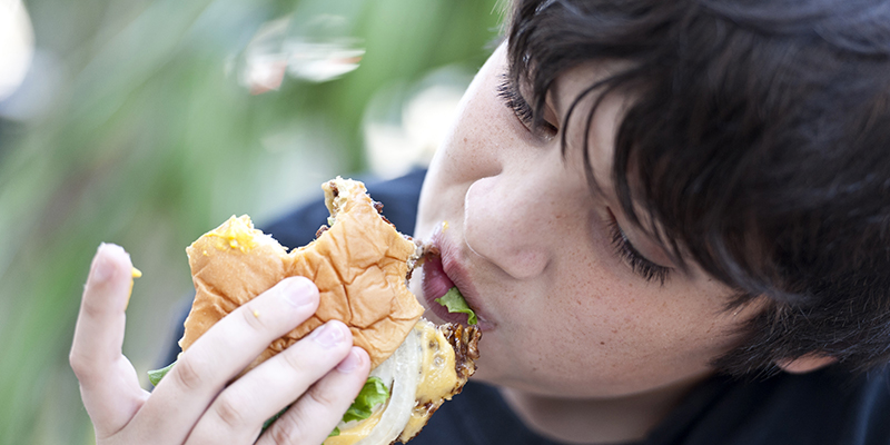 Close up of a child eating a burger