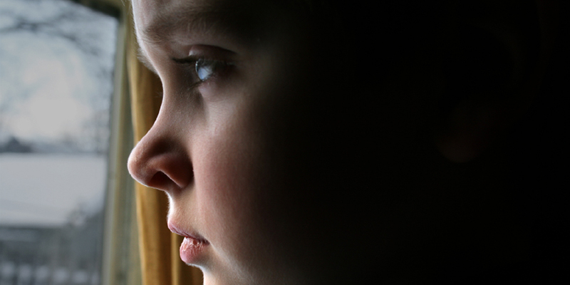 sad child looking out of window