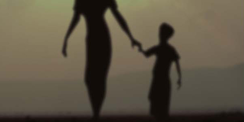 Silhouette of woman holding a child