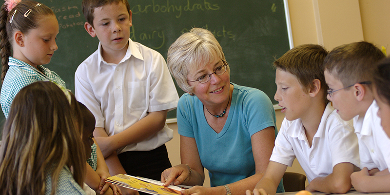 A school nurse speaks to children