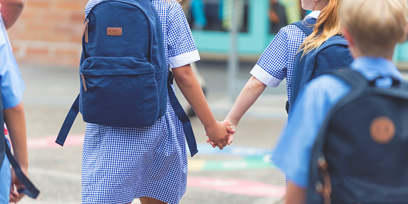 Children in school uniforms hold hands