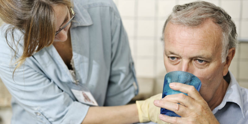 Nursing professional caring for patient with dysphagia