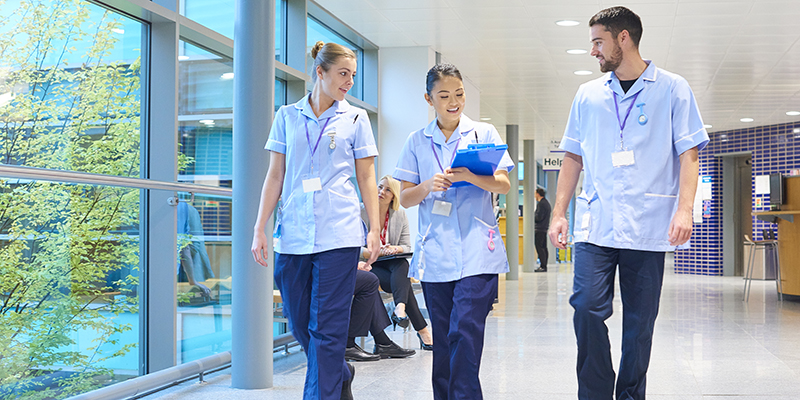 Three nurses walking down a corridor