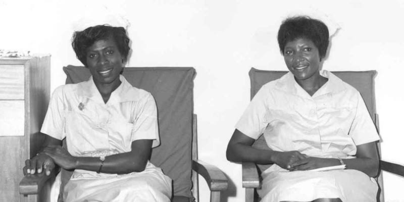 Two nurses sat next to one another in chairs