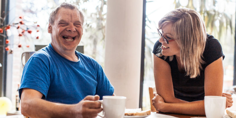 Man with learning disability laughing with carer