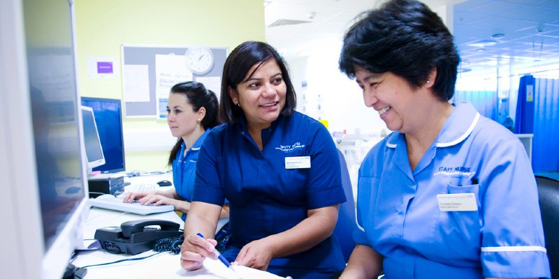 Two nursing staff at a desk smiling