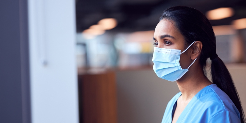 A female nurse wearing a face mask looks concerned