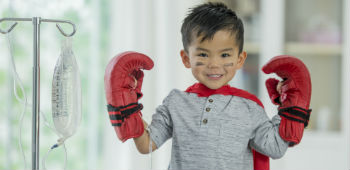 Little boy is hospital posing with boxing gloves