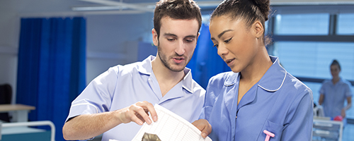 Two nurses discussing patient information