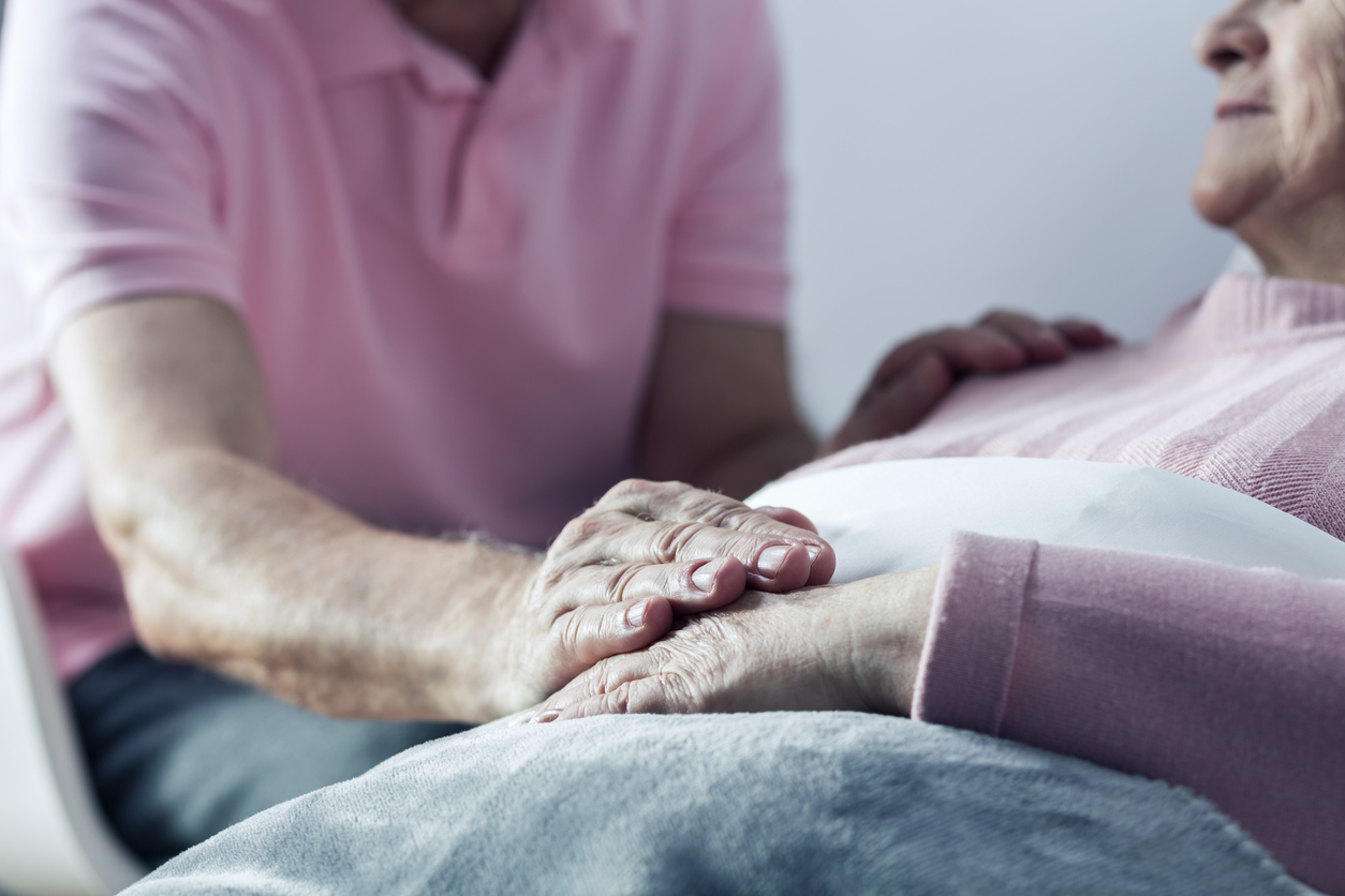 carer holding hand of elderly person