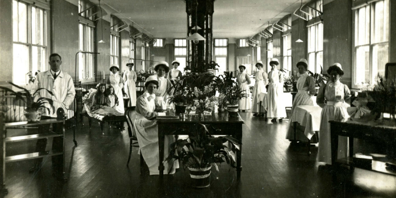 Black and white postcard image of the interior of a diptheria ward at Leeds City Hospital, Seacroft. The portrait contains nurses, doctors and two child patients.