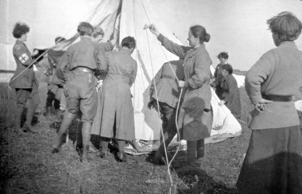 Women of the Scottish Women's Hospitals group pitching Bell tents including some in VAD uniform (with armband), Romania.