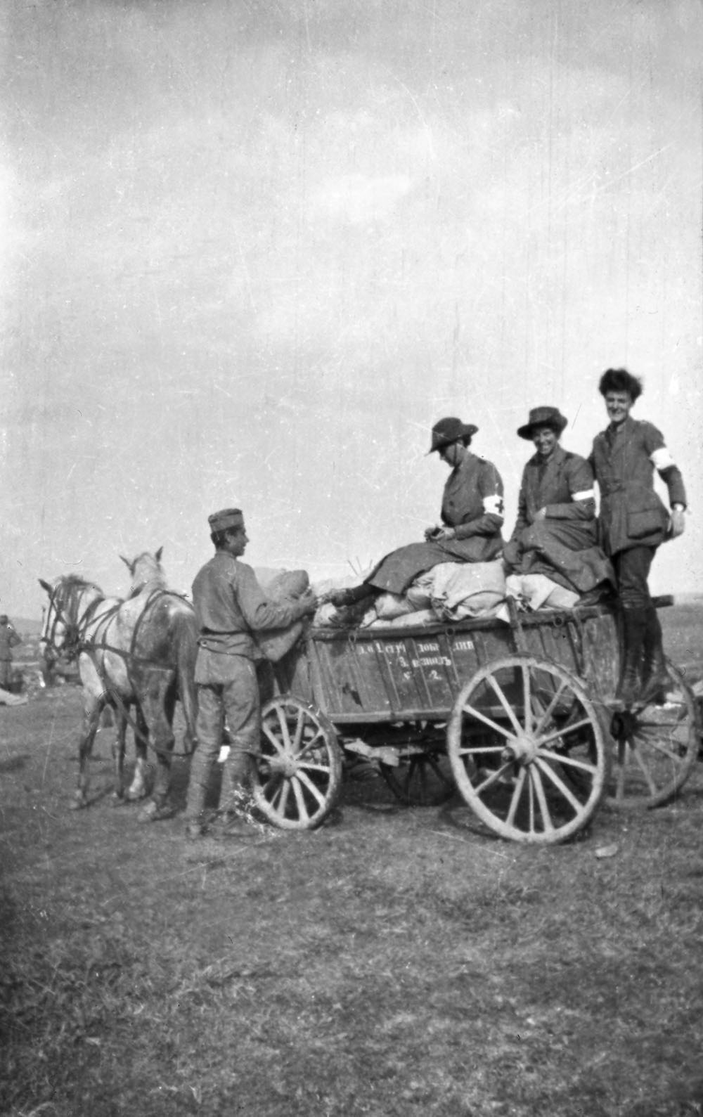 Three orderlies on cart in the uniform of the Scottish Women's Hospitals group, Romania.