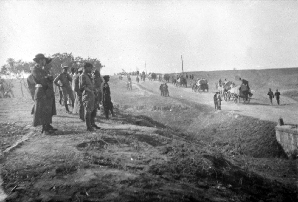 A view of road with staff watching either soldiers on the move or refugees fleeing, Romania.