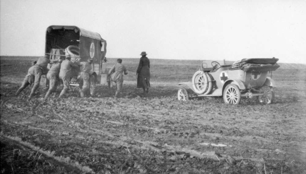 Four soldiers pushing ambulance stuck in the mud, an orderly in cart and an ambulance car in the mud, Romania.